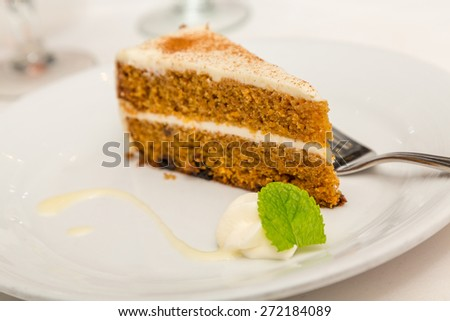Slice of carrot cake on a white plate with dollop of whipped cream and mint leaf - stock photo