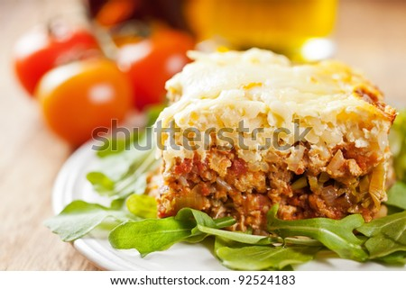 Slice of casserole with brown rice, minced turkey meat and leeks with cheese on top decorated with arugula on the white plate - stock photo