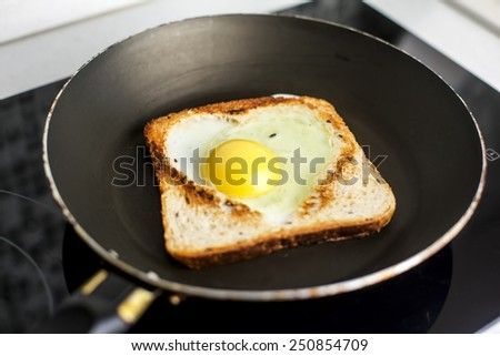 Slice of cereal toast bread with cut out heart shape full egg on black pan - stock photo