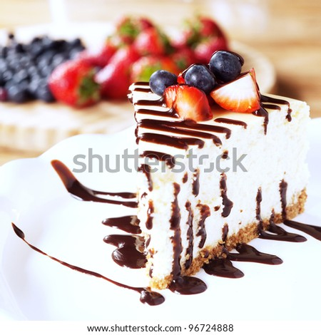 Slice of cheesecake topped with strawberries and blueberries - stock photo