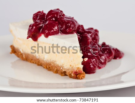 Slice of cheesecake with cherry sauce on top - stock photo
