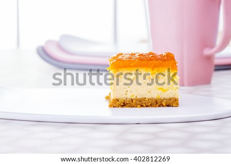Slice of cheesecake  with oranges confiture jelly on white ceramic plate on the table and elegance pink cup of tea on white window background, New York Cheesecake  - stock photo