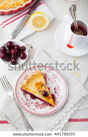 Slice of cherry pie on a ceramic plate. White textile background. Top view. Copy space - stock photo