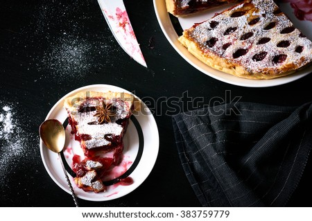 Slice of cherry pie on a plate. Homemade cherry cake on black background. Top view. Selective focus - stock photo