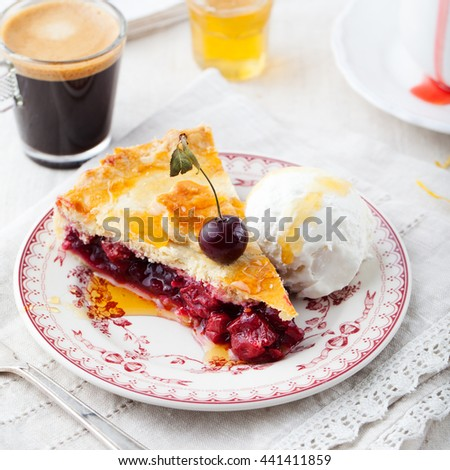Slice of cherry pie with ice cream on a white textile background - stock photo