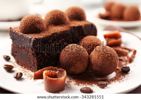 Slice of chocolate cake with a truffle on plate closeup - stock photo