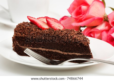Slice of chocolate cake with strawberries and red roses as a background - stock photo