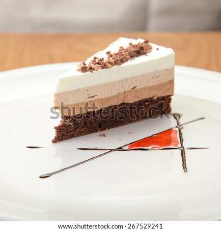 Slice of chocolate coffee cake on wooden table - stock photo