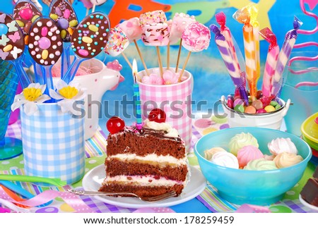 slice of chocolate torte with candle and homemade sweets for children birthday party - stock photo