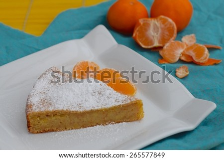 Slice of clementine cake garnish with icing sugar