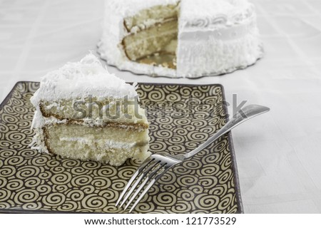slice of coconut cake on a plate with a fork and the whole cake in the background - stock photo