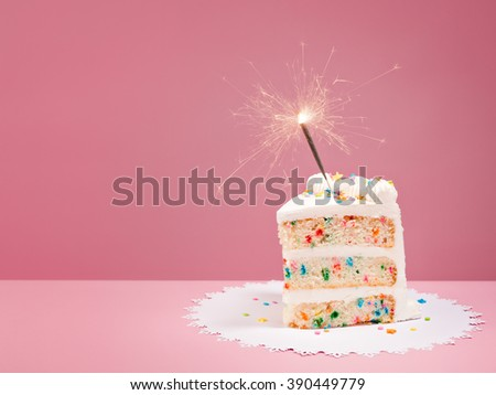 Slice of Colorful Birthday Confetti Cake with a lit sparkler over a pink background. - stock photo