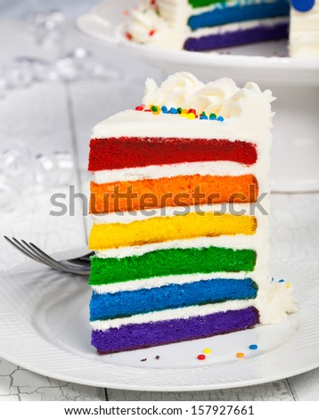 Slice of colourful rainbow layered birthday cake. - stock photo