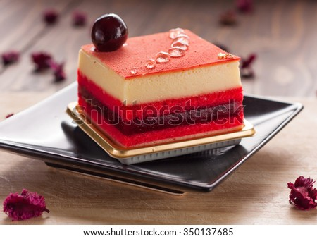 Slice of delicious Berry mousse cake decorate with syrap and blueberry on wood table - stock photo