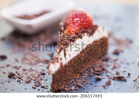 Slice of delicious chocolate and mascarpone cake with a fresh strawberry and roughly chopped chocolate flakes. Shallow depth of field