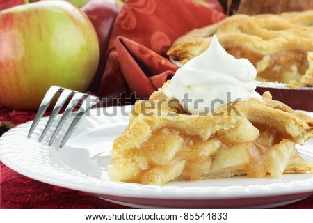 Slice of delicious fresh baked apple pie with whipped cream. Extreme shallow depth of field with selective focus on slice of pie. - stock photo