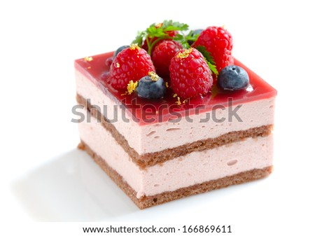 Slice of delicious layered and glazed raspberry mousse cake decorated with fresh blueberries, raspberries, sprig of chervil, and pieces of edible gold leaf - stock photo