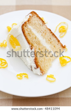 Slice of delicious lemon sponge cake with lemon rind on a white plate