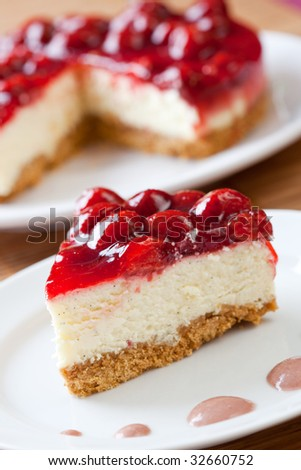 Slice of delicious strawberry cheese cake with a cake in the background