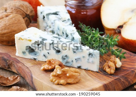 Slice of French Roquefort cheese accompanied with walnuts, pears and fresh thyme - stock photo