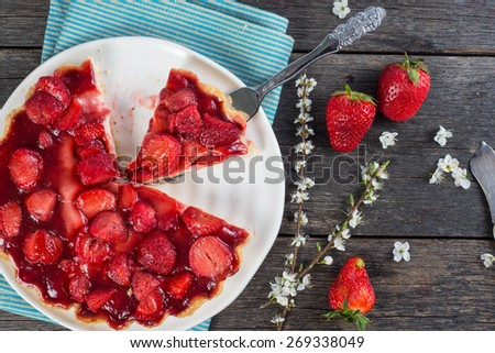slice of fresh homemade strawberry tart with flowers from above on wooden table - stock photo