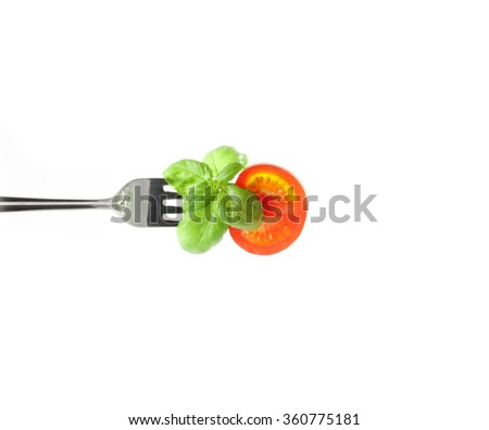 slice of fresh tomato and basil on a fork on a white background - stock photo