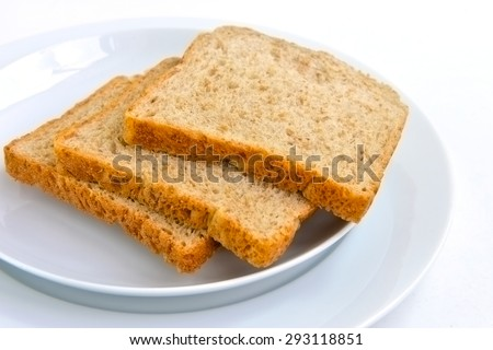 Slice of fresh wholemeal bread with plate isolated on white background, selective focus.  - stock photo