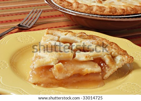 Slice of freshly baked apple pie on decorative plate.  Colorful tablecloth and whole pie in background.  Macro with shallow dof. - stock photo