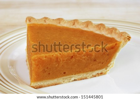 Slice of freshly baked pumpkin pie.  Closeup with shallow dof. - stock photo