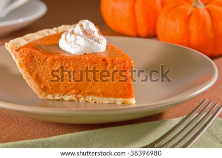 Slice of freshly cut pumpkin pie with whipped cream cinnamon and nutmeg - stock photo