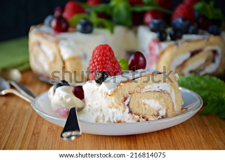 Slice of frozen no bake cheesecake with swiss roll base topped with fresh summer berries on white dessert plate, close up - stock photo