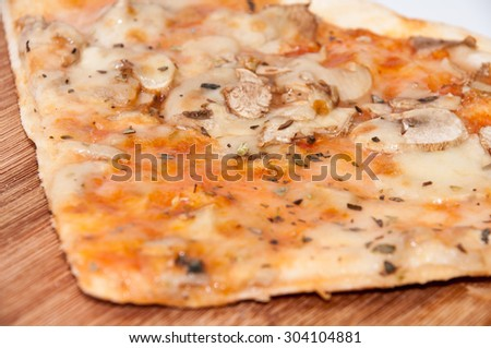 Slice of fungi pizza on the wooden board. - stock photo