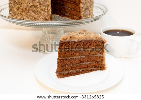 Slice of german chocolate cake removed from whole cake which is in background along with cup of coffee.  Isolated on white background. - stock photo