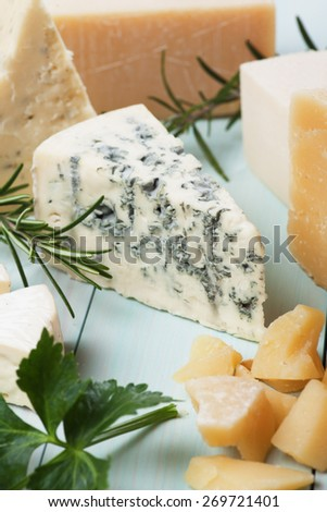 Slice of gorgonzola cheese with herbs and other cheeses - stock photo