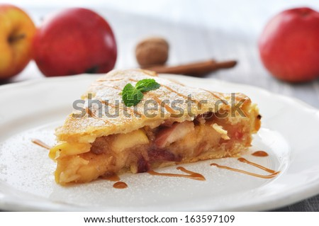 Slice of homemade apple pie with fresh apples on wooden background - stock photo