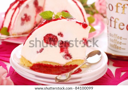 slice of homemade cold cheese cake with fresh raspberries and poured fruit sauce