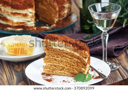 Slice of homemade layered honey cake with honeycomb and mint, traditional food of Jewish New Near. Sweet food