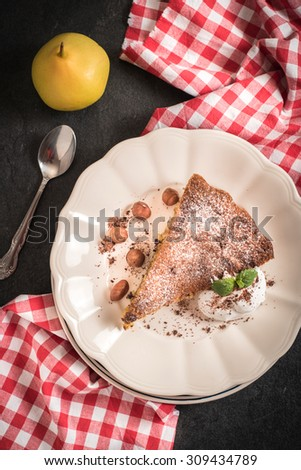 Slice of homemade pear pie with nougat and sweet vanilla cream,from above  - stock photo