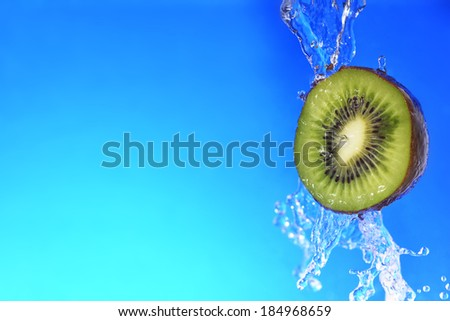 slice of kiwi in the water with bubbles, on blue background - stock photo