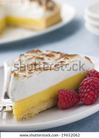 Slice Of Lemon Meringue Pie With Raspberries - stock photo