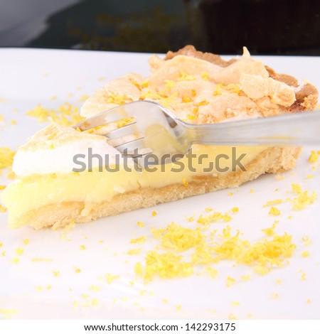 Slice of Lemon Meringue Tart being eaten with a fork - stock photo