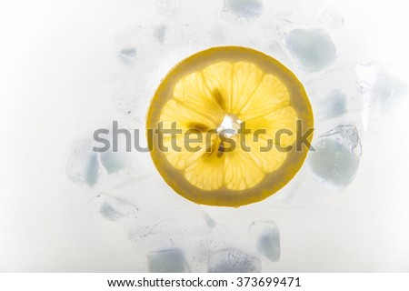 Slice of lemon with ice cubes with backlight - stock photo