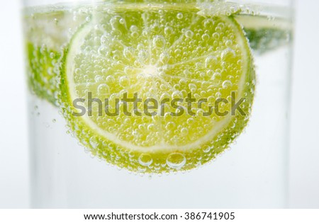 slice of lime and soda in the water with bubbles - stock photo