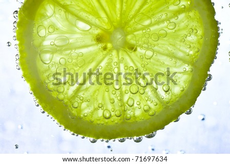slice of lime in the water with bubbles - stock photo