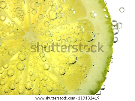 slice of lime in the water with bubbles, isolated on white - stock photo