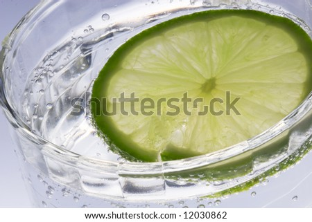 Slice of lime in water - stock photo