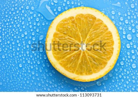 Slice of lime with drop on blue background - stock photo