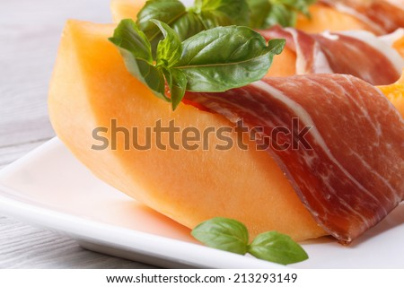 slice of melon wrapped in prosciutto and green basil on a white plate on the table. horizontal macro  - stock photo