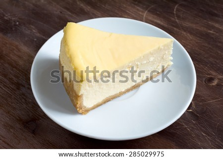 Slice of New York cheesecake on white plate on brown wooden table - stock photo