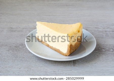 Slice of New York cheesecake on white plate on gray background, isolated - stock photo